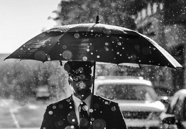 傘をさしたスーツ姿の男性の写真