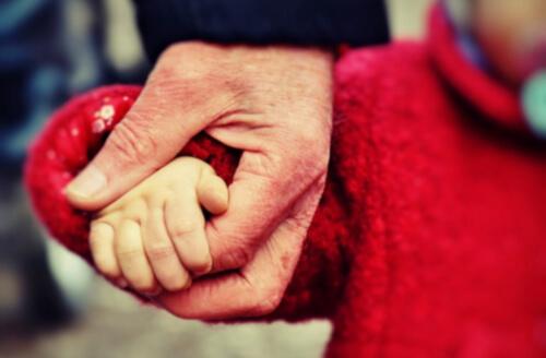 おじいちゃんと孫が手をつないでいる写真